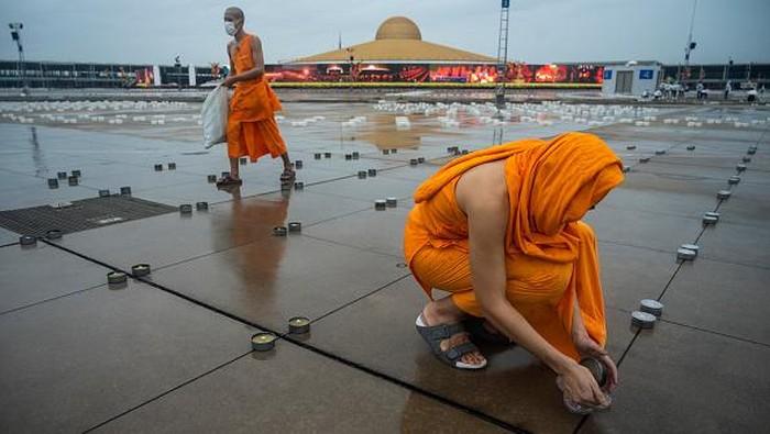 Umat Buddha di Thailand merayakan Hari Asalha Puja di tengah pandemi Corona. Ribuan lilin disiapkan untuk menerangi kuil saat perayaan Asalha Puja.