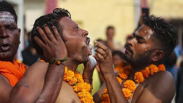 Para penyembah Nampak terlihat kesakitan saat wajah, perut dan anggota tubuh lainnya ditusuk batang logam.