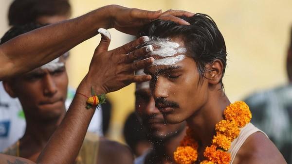Sebelum melakukan ritual ziarah tahunan kuil dewi Hindu Sheetla Mata, penyembah meletakkan abu di dahi sebagai bagian dari ritual tersebut.