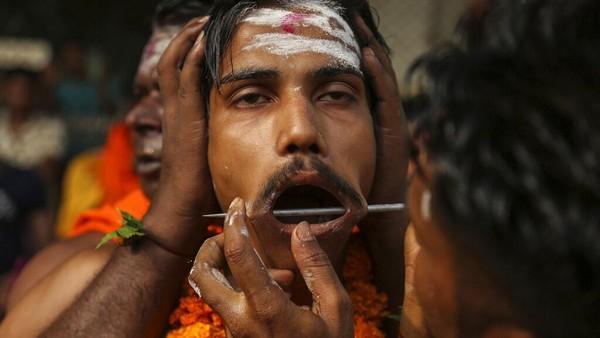 Bukan hanya di Indonesia, India juga memiliki tradisi menusukkan besi ke pipi hingga tembus layaknya tatung maupun debus.