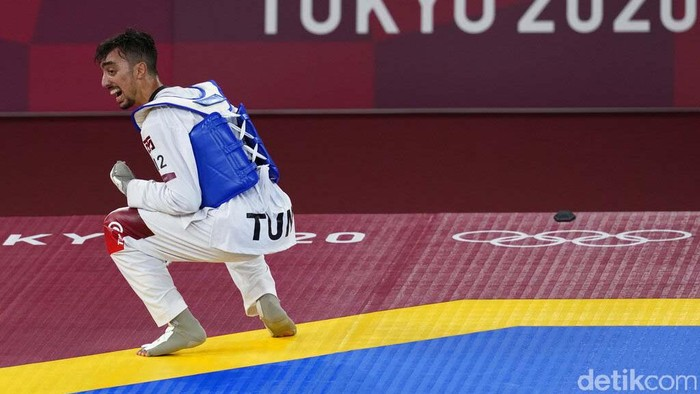 Tunisia's Mohamed Khalil Jendoubi celebrates after defeating South Kore's Jang Jun to winning a gold medal during the men's 58kg taekwondo match at the 2020 Summer Olympics, Saturday, July 24, 2021, in Tokyo, Japan. (AP Photo/Themba Hadebe)