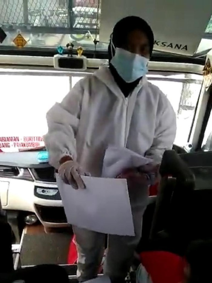 Video seorang wanita berbaju hazmat disebut menjual surat bebas COVID-19 kepada penumpang bus (Screenshot video viral)