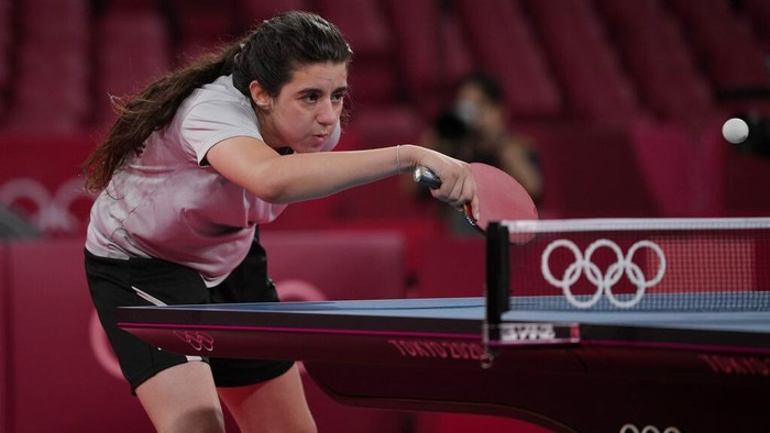 Syria's Hend Zaza catches a ball during women's table tennis singles preliminary round match against Austria's Liu Jia at the 2020 Summer Olympics, Saturday, July 24, 2021, in Tokyo. (AP Photo/Kin Cheung)