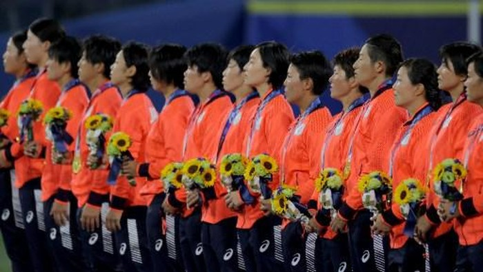 Gold medal winner, Japans softball player listen to the national anthem on the podium during the medal ceremony for the softball competition in the Tokyo 2020 Olympic Games at the Yokohama Baseball Stadium in Yokohama, Japan, on July 27, 2021. (Photo by KAZUHIRO FUJIHARA / AFP)