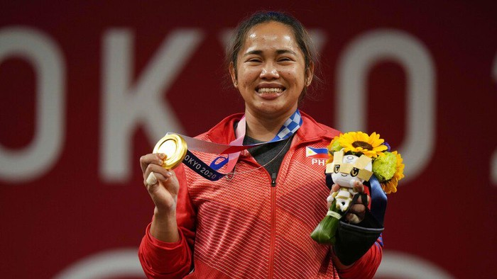 Hidilyn Diaz of Philippines celebrates with Weightlifting Philippines federation president Monico Puntuevella after winning the gold medal in the womens 55kg weightlifting event, at the 2020 Summer Olympics, Monday, July 26, 2021, in Tokyo, Japan. (AP Photo/Luca Bruno)