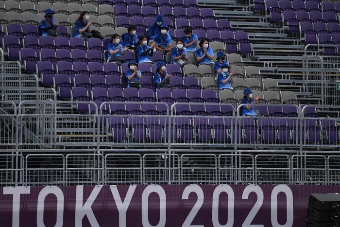 Sejumlah relawan beristirahat sambil memberikan dukungan saat pertandingan panahan Olimpiade Tokyo 2020 di Yumenoshima Park Archery Field, Tokyo, Jepang, Senin (26/7/2021). Penyelenggaraan Olimpiade yang diselenggarakan tanpa penonton dari kalangan umum tersebut merupakan keputusan di tengah kondisi darurat COVID-19 yang sedang diberlakukan di Ibu Kota Jepang. ANTARA FOTO/Sigid Kurniawan/wsj.