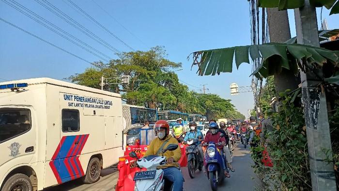 Antrean kendaraan mengular di titik penyekatan Pesing, Jakarta Barat, Selasa (27/7/2021).