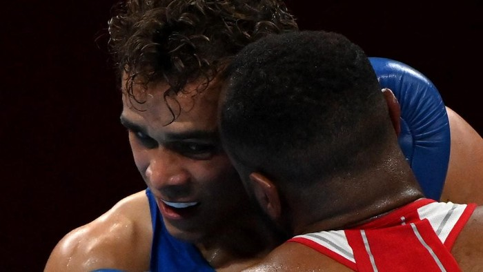 Moroccos Youness Baalla (red) and New Zealands David Nyika fight during their mens heavy (81-91kg) preliminaries round of 16 boxing match during the Tokyo 2020 Olympic Games at the Kokugikan Arena in Tokyo on July 27, 2021. (Photo by Luis ROBAYO / AFP)