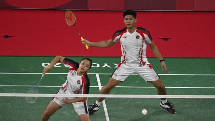 Indonesias Melati Daeva Oktavianti (L) and Indonesias Praveen Jordan watch the shuttlecock during their mixed doubles badminton quarter final match against Chinas Zheng Siwei and Chinas Huang Yaqiong during the Tokyo 2020 Olympic Games at the Musashino Forest Sports Plaza in Tokyo on July 28, 2021. (Photo by Alexander NEMENOV / AFP)