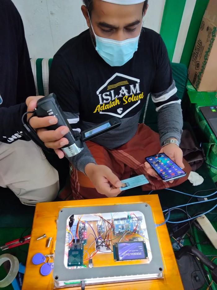 Habib Fathurrahman Bahasyim memperlihatkan alat Smart Checker pemindai e-KTP yang bisa digunakan untuk mengecek peserta vaksinasi. (Muhammad Risanta/detikcom)