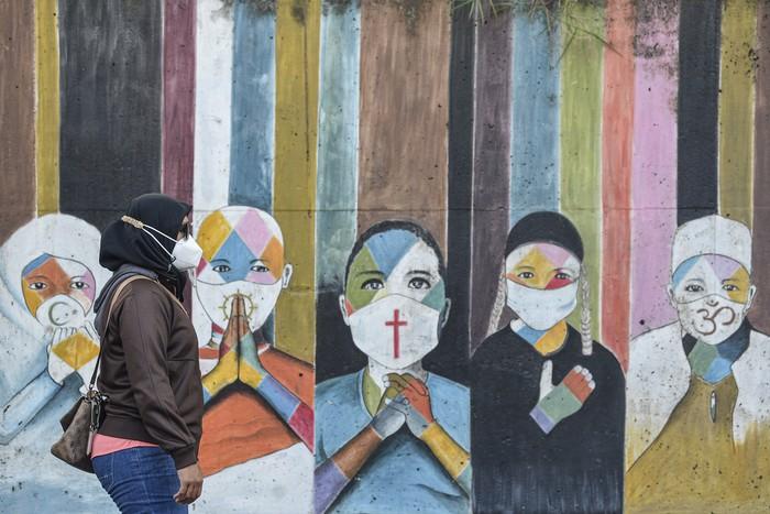 Seorang warga dengan mengenakan masker berjalan di depan mural imbauan mengenakan masker dari lintas agama di kawasan Jakarta Timur.