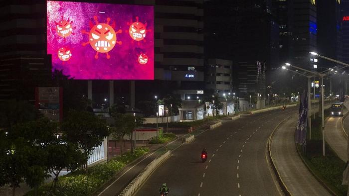 Suasana malam hari saat Pemberlakuan Pembatasan Kegiatan Masyarakat (PPKM) Darurat di kawasan jalan Sudirman, Jakarta.