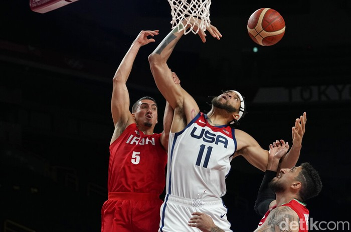 United States' Javale Mc Gee (11), center, is fouled by Iran's Pujan Jalalpoor (5), left, during men's basketball preliminary round game at the 2020 Summer Olympics, Wednesday, July 28, 2021, in Saitama, Japan. (AP Photo/Eric Gay)