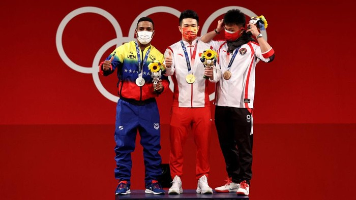 TOKYO, JAPAN - JULY 28:  (L-R) Silver medalist Julio Ruben Mayora Pernia of Team Venezuela, gold medalist Zhiyong Shi of Team China and bronze medalist Rahmat Erwin Abdullah of Team Indonesia pose during the medal ceremony for the Weightlifting - Mens 73kg Group A on day five of the Tokyo Olympic Games at Tokyo International Forum on July 28, 2021 in Tokyo, Japan. (Photo by Chris Graythen/Getty Images)