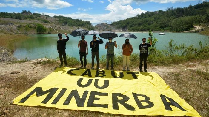 Sejumlah pengabdi bantuan hukum (PBH) LBH Padang, melakukan aksi guna menuntut pencabutan UU Minerba di kawasan lubang tambang batubara di Talawi, Sawahlunto, Sumatera Barat, Kamis (29/7/2021). Aksi tersebut digelar untuk mendukung Hak Uji Materil Undang-undang Mineral dan Batubara (UU-Minerba) ke Mahkamah Konstitusi yang dilakukan YLBHI, Jatam, LBH Bandung, LBH Padang, warga Banyuwangi dan warga Bangka Belitung, agar undang-undang tersebut dicabut karena dinilai sangat berdampak buruk terhadap lingkungan.  ANTARA FOTO/Iggoy el Fitra/aww.