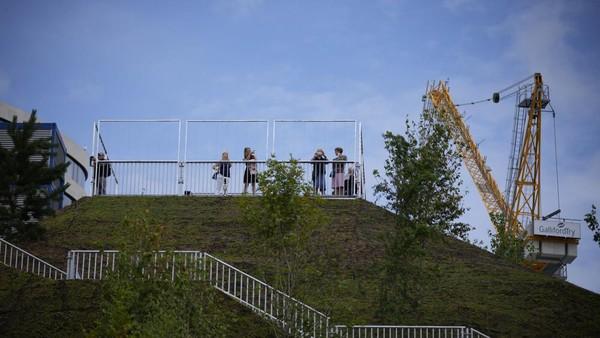 Bukit buatan berwarna hijau di London diklaim bisa menjadi tempat untuk melihat keindahan kota dari ketinggian. (Matt Dunham/AP)