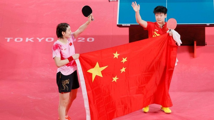 TOKYO, JAPAN - JULY 29: Chen Meng (L) and Sun Yingsha (R) hold up the flag of Team China after Chen won their Singles Gold Medal match on day six of the Tokyo 2020 Olympic Games at Tokyo Metropolitan Gymnasium on July 29, 2021 in Tokyo, Japan. (Photo by Steph Chambers/Getty Images)
