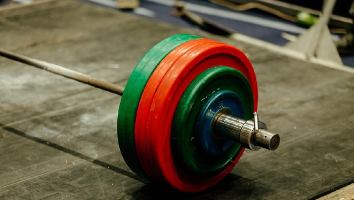 barbell with green and red plates on platform for powerlifting