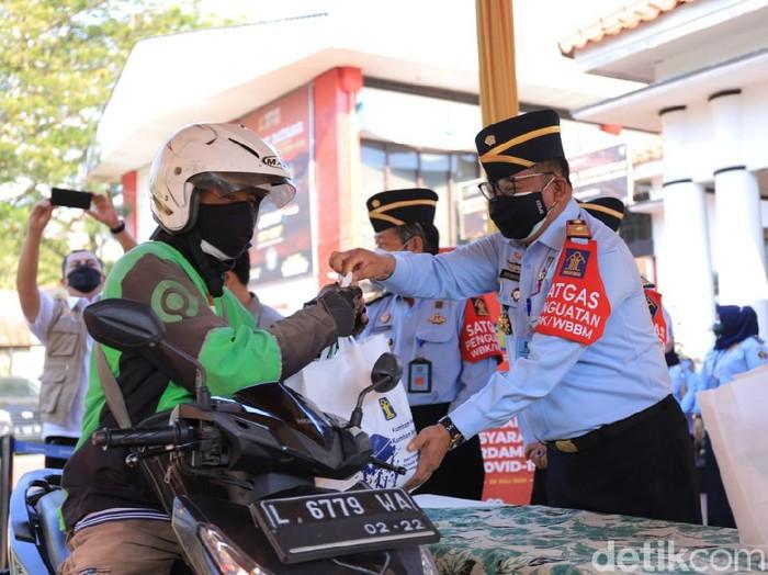 Ojol di Surabaya mendapat paket sembako secara drive thru dari KemenkumHam Jatim. Bantuan itu diberikan untuk meringankan beban di tengah pandemi COVID-19.