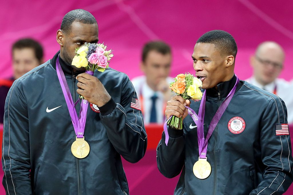 LONDON, ENGLAND - AUGUST 12:  Gold medallists LeBron James #6 of the United States and Russell Westbrook #7 of the United States smell their ceremonial flowers on the podium during the medal ceremony for the Men's Basketball on Day 16 of the London 2012 Olympics Games at North Greenwich Arena on August 12, 2012 in London, England.  (Photo by Streeter Lecka/Getty Images)