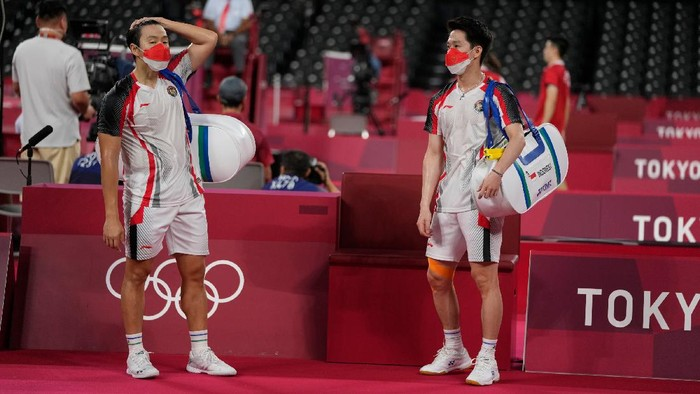 Indonesias Marcus Fernaldi Gideon, left, and Kevin Sanjaya Sukamuljo react after beaten by Malaysias Aaron Chia and Soh Wooi Yik in their mens doubles quarterfinal match at the 2020 Summer Olympics, Thursday, July 29, 2021, in Tokyo, Japan. (AP Photo/Markus Schreiber)