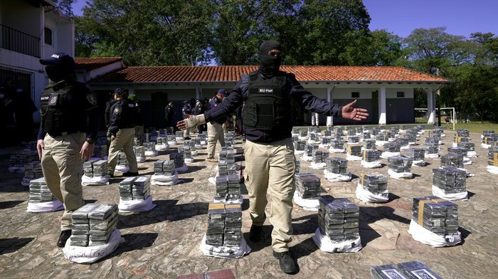 Police stand guard over seized cocaine that is displayed to the press at the Special Forces Police headquarters in Asuncion, Paraguay, Wednesday, July 28, 2021. According Interior Minister Arnaldo Giuzzio, a record amount of 3,415 kilograms (7,528 pounds) of cocaine was found in sacks of organic sugar in a warehouse in the city of Fernando de la Mora on July 27. (AP Photo/Jorge Saenz)