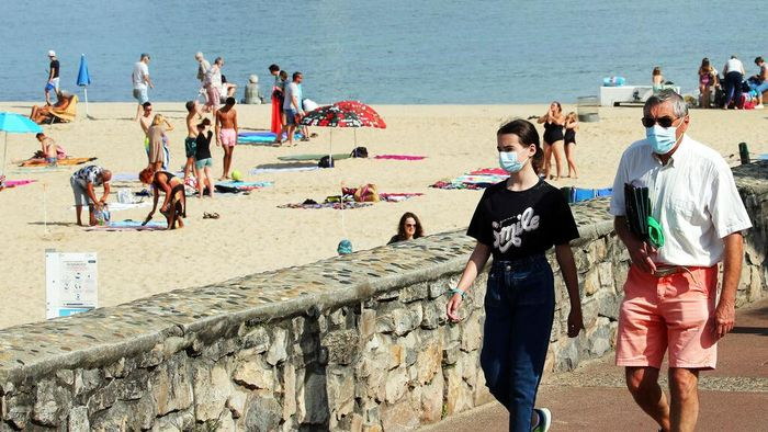 People wearing face masks to protect against coronavirus walk on the pedestrian promenade along the beach in Biarritz, southwestern France, Wednesday, July 28, 2021. Local authorities in France are re-imposing mask mandates and other virus restrictions because of fast-growing infections with the delta variant, which is causing COVID-19 hospitalizations in France to rise again. (AP Photo/Bob Edme)