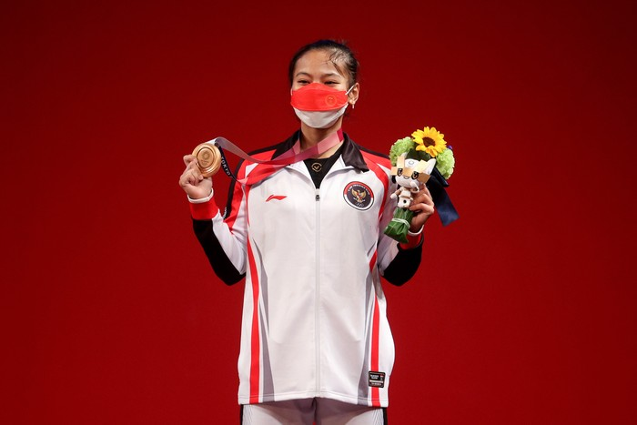 TOKYO, JAPAN - JULY 24: Bronze medalist Windy Cantika Aisah of Team Indonesia poses with the bronze medal for the Weightlifting - Womens 49kg Group A on day one of the Tokyo 2020 Olympic Games at Tokyo International Forum on July 24, 2021 in Tokyo, Japan. (Photo by Chris Graythen/Getty Images)