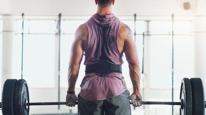 Rearview shot of a muscular man lifting a barbell in a gym