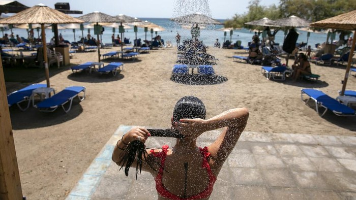 Pantai hingga pancuran umum di Yunani ramai didatangi warga. Mereka datang untuk mendinginkan diri imbas gelombang panas yang tengah melanda kawasan itu.