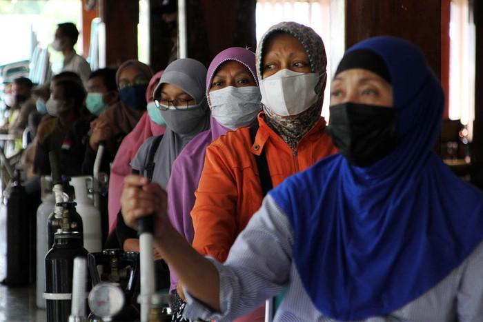 Warga mengantre untuk melakukan isi ulang oksigen pada kegiatan bakti sosial oksigen tanpa dipungut biaya di Rumah Dinas Bupati Karanganyar, Jawa Tengah, Jumat (30/7).