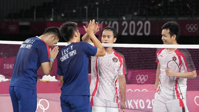 Taiwans Lee Yang, center left, and Wang Chi-Lin, left, talk to Indonesias Mohammad Ahsan and Hendra Setiawan after wining their mens doubles badminton semifinal match against them at the 2020 Summer Olympics, Friday, July 30, 2021, in Tokyo, Japan. (AP Photo/Markus Schreiber)