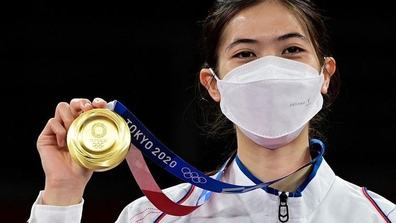 Thailands Panipak Wongpattanakit celebrates with her gold medal on the podium after winning the taekwondo womens -49kg gold medal bout during the Tokyo 2020 Olympic Games at the Makuhari Messe Hall in Tokyo on July 24, 2021. (Photo by Javier SORIANO / AFP)