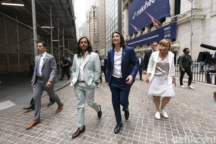 Baiju Bhatt, left, and Vladimir Tenev, Co-Founders of Robinhood, walk on Wall Street following their company's IPO at Nasdaq, Thursday, July 29, 2021 in New York. Robinhood is selling its own stock on Wall Street, the very place the online brokerage has rattled with its stated goal of democratizing finance. Through its app, Robinhood has introduced millions to investing and reshaped the brokerage industry, all while racking up a long list of controversies in less than eight years. (AP Photo/Mark Lennihan)
