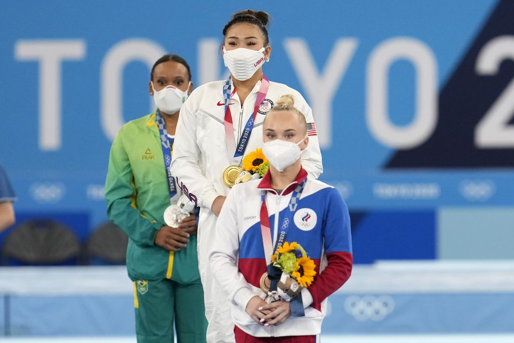 From left to right, silver medallist Brazil's Rebeca Andrade, Gold medallist Sunisa Lee of the Unites States, and bronze medallist Angelina Melnikova, of the Russian Olympic Committee, celebrate during the medal ceremony for the artistic gymnastics women's all-around at the 2020 Summer Olympics, Thursday, July 29, 2021, in Tokyo.(AP Photo/Natacha Pisarenko)