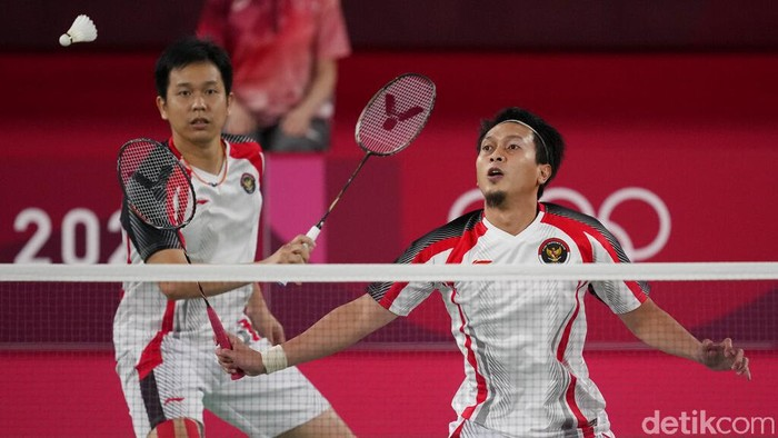 Taiwan's Lee Yang, left, and Wang Chi-Lin talk to Indonesia's Mohammad Ahsan and Hendra Setiawan after wining their men's doubles badminton semifinal match at the 2020 Summer Olympics, Friday, July 30, 2021, in Tokyo, Japan. (AP Photo/Dita Alangkara)