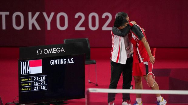 Indonesia's Anthony Sinisuka Ginting celebrates with his coach Henry Saputra Ho after defeating Anders Antonsen of Denmark during their men's singles badminton quarterfinal match at the 2020 Summer Olympics, Saturday, July 31, 2021, in Tokyo, Japan. (AP Photo/Dita Alangkara)