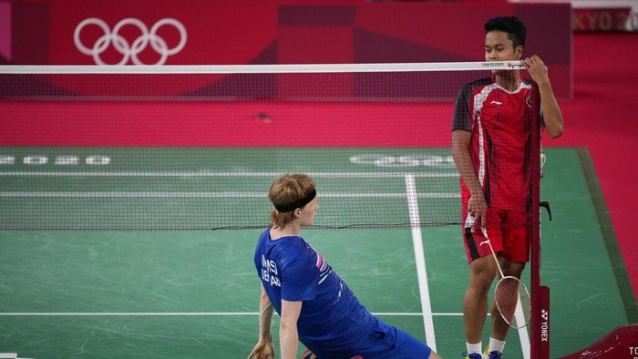 Indonesias Anthony Sinisuka Ginting, right, and Anders Antonsen of Denmark react after a long rally during their mens singles badminton quarterfinal match at the 2020 Summer Olympics, Saturday, July 31, 2021, in Tokyo, Japan. (AP Photo/Dita Alangkara)