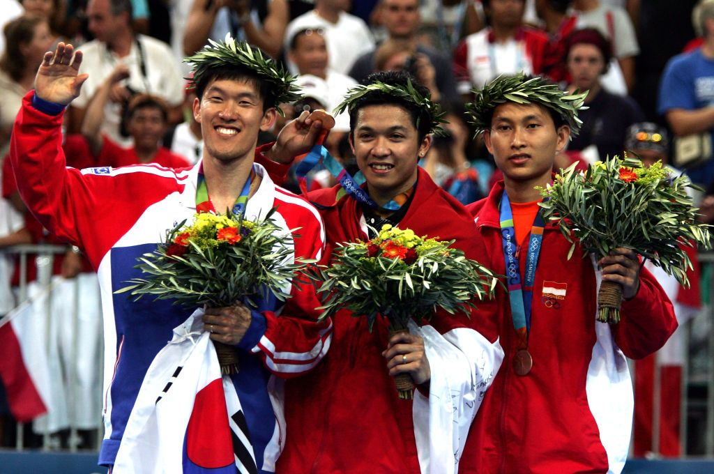 ATHENS - AUGUST 21:  (L-R) Seung Mo Shon of Korea (silver), Taufik Hidayat of Indonesia (gold) and Soni Dwi Kuncoro of Indonesia (bronze) celebrate after receiving medals  for the men's singles badminton event on August 21, 2004 during the Athens 2004 Summer Olympic Games at Olympic Hall in the Goudi Olympic Complex in Athens, Greece. (Photo by Jonathan Ferrey/Getty Images)