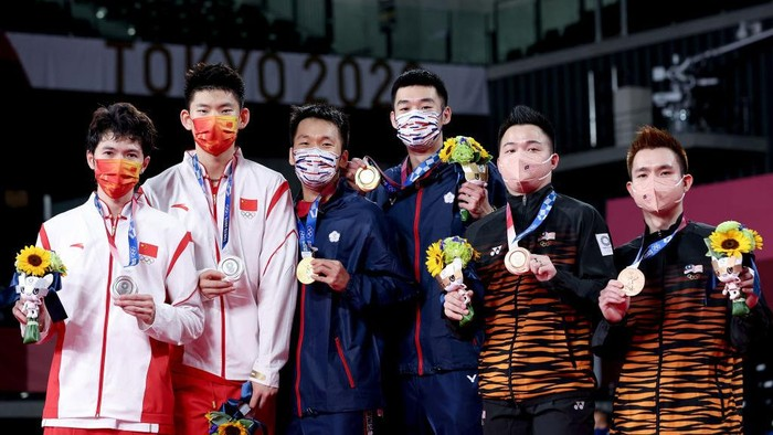 CHOFU, JAPAN - JULY 31:  (L-R) Silver medalists Li Jun Hui and Liu Yu Chen of Team China, gold medalists Lee Yang and Wang Chi-Lin of Team Chinese Taipei and bronze medalists Aaron Chia and Soh Wooi Yik of Team Malaysia pose on the podium during the medal ceremony for the Mens Doubles badminton event on day eight of the Tokyo 2020 Olympic Games at Musashino Forest Sport Plaza on July 31, 2021 in Chofu, Tokyo, Japan.  (Photo by Lintao Zhang/Getty Images)