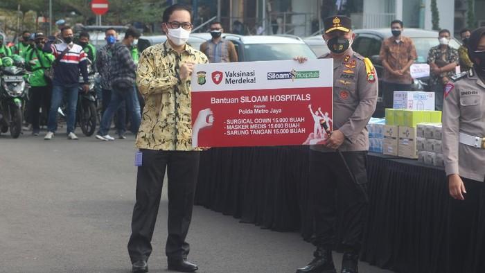 Chief Network Officer Siloam Hospitals Group Hendy Widjaja (kanan) menyerahkan donasi Siloam Hospitals Group kepada Kapolda Metro Jaya Irjen Fadil Imran berupa 15000 Surgical Gown, 15000 Masker Media, 15000 Sarung Tangan Medis di Lapangan Presisi Polda Metro Jaya, Jakarta, Jumat (30/7/2021). Bantuan medis dari Siloam Hospitals Group kepada Polda Metro Jaya sebagai wujud nyata peran serta Siloam Hospitals Group ambil bagian dari Program Vaksinasi Merdeka sebagai upaya memutus rantai pandemi Covid-19.