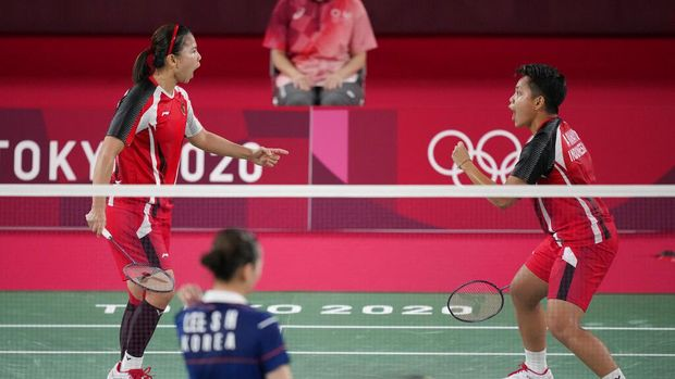 Indonesia's Greysia Polii, left, and Apriyani Rahayu celebrate after scoring a point against South Korea's Lee Sohee and Shin Seungchan during their women's semi-final badminton match at the 2020 Summer Olympics, Saturday, July 31, 2021, in Tokyo, Japan. (AP Photo/Dita Alangkara)