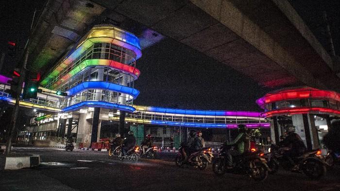 Seorang perempuan duduk di atas pembatas jalan di dekat halte Centrale Stichting Wederopbouw (CSW) yang berhiaskan lampu warna-warni di Kawasan Kebayoran Baru, Jakarta, Sabtu (31/7/2021). Proyek pembangunan jembatan penghubung atau skybridge untuk intergrasi Halte Transjakarta CSW dengan Stasiun MRT ASEAN itu mengusung konsep desain Cakra Selaras Wahana yang memiliki arti sebagai lingkaran penghubung yang setara antar moda. ANTARA FOTO/Aprillio Akbar/wsj.
