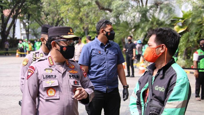 Kapolri Jenderal Listyo Sigit Prabowo berbincang dengan driver ojol di lokasi penyaluran bansos online