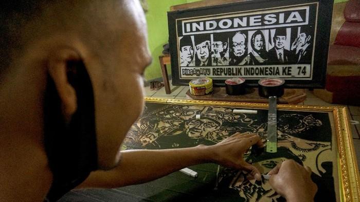 Perajin memproduksi lukisan siluet berbahan lakban di Studio Lukisan Galak, Desa Kemiri Barat, Subah, Kabupaten Batang, Jawa Tengah, Sabtu (31/7/2021). Untuk mempertahankan penjualan saat pandemi COVID-19, perajin lukisan itu memanfaatkan daring untuk memasarkan karyanya hingga ke Lampung dengan dijual antara Rp80 ribu-Rp1 juta per lukisan berbagai macam ukuran dengan waktu pengerjaan 2-3 hari. ANTARA FOTO/Harviyan Perdana Putra/wsj.