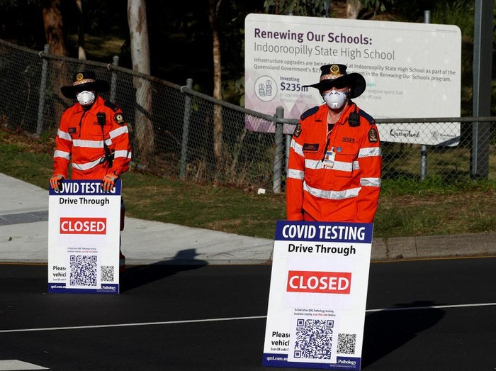 Volunteers direct traffic at a Covid-19 drive-through testing clinic in eastern Brisbane on July 31, 2021, as Australias third-largest city Brisbane and other parts of Queensland state will enter a snap Covid-19 lockdown. (Photo by Patrick HAMILTON / AFP)