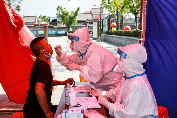 The photo taken on July 30, 2021 shows a man receiving nucleic acid testing for the Covid-19 coronavirus in Huaian, in eastern Chinas Jiangsu province, as China raced to contain its worst coronavirus outbreak in months. (Photo by STR / AFP) / China OUT