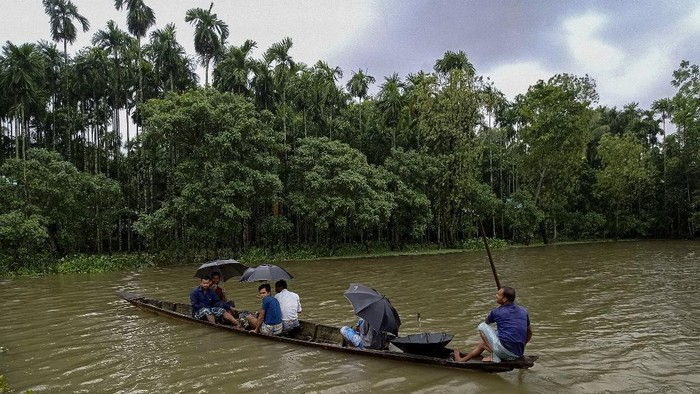 Locals use a boat to reach towards a shelter after their houses were submerged in flood waters at Maulovir Para, Coxs Bazar on July 30, 2021 after monsoon floods and landslides have cut off more than 300,000 people in villages across southeast Bangladesh and killed at least 20 people including six Rohingya refugees. (Photo by Tanbir MIRAJ / AFP)