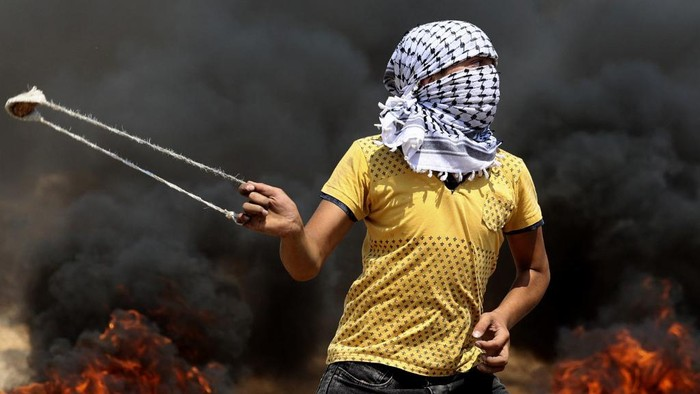 A Palestinian uses a slingshot to hurl stones during clashes with Israeli forces in the village of Beita in the north of the occupied West Bank on July 30, 2021. (Photo by JAAFAR ASHTIYEH / AFP)