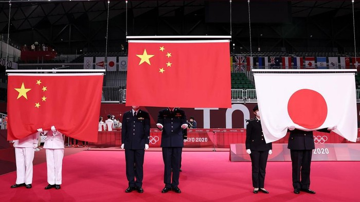 CHOFU, JAPAN - JULY 30: National flags of China and Japan are prepared to be raised during the medal ceremony for the Mix Doubles badminton event on day seven of the Tokyo 2020 Olympic Games at Musashino Forest Sport Plaza on July 30, 2021 in Chofu, Tokyo, Japan. (Photo by Lintao Zhang/Getty Images)